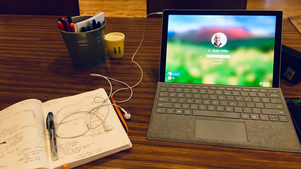 Photo of a notebook with a pen and a Microsoft Surface Pro